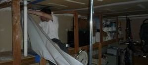 Water and Mold Damage Restoration Technician Removing Vapor Barrier