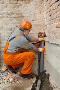 911-restoration-Home renovation, plumber fixing sewerage pipe at construction site-Manhattan